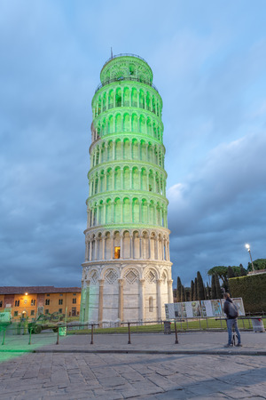 PISA, ITALY - MARCH 17, 2019: Pisa Tower for St Patricks Day illuminated by green lights..