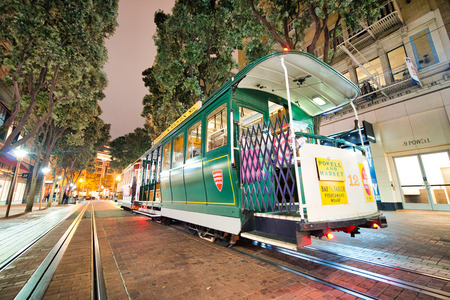 SAN FRANCISCO, CA - AUGUST 7, 2017: Night view of cable car in Market Street. The city attracts 20 million tourists annually.