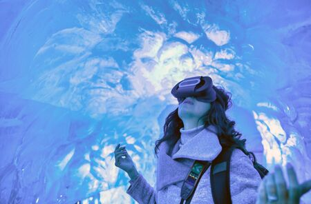 Woman with 3D glasses visor enjoying the view of Iceland ice cave.