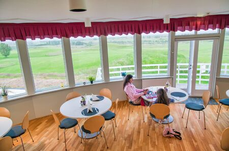 Mother and daughter relaxing in a room with landscape view.