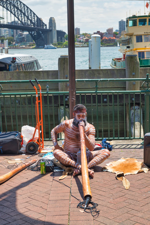 SYDNEY - OCTOBER 2015: An unidentified aboriginal man with didgeridoo busking (performing for passing tourists) at Circular Quay.