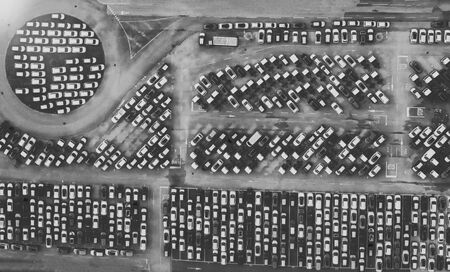 Overhead aerial view photo vehicle lot showing new produced cars by automakers stored there for further distribution towards car dealers port area where ships bring vehicles in mass production scene.