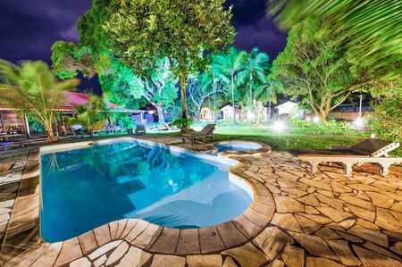 Beautiful garden with trees, pool and grass at night. Reklamní fotografie