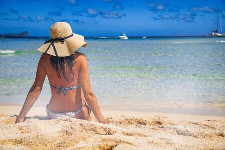 Beautiful woman wearing straw hat on the shoreline, back view, holiday concept. Standard-Bild - 143183926