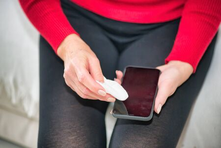 Woman cleaning smartphone screen with soft cloth. Coronavirus prevention and home disinfection.