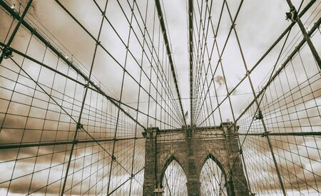 The Brooklyn Bridge at sunset, major pylon and cables against cloudy sky, New York City