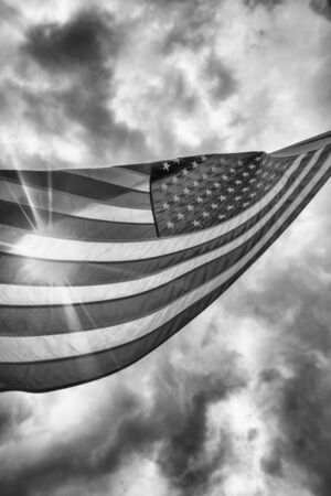 Flag of the United States with sunflare and cloudy sky. USA patriotism concept, backlit scene.