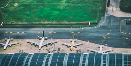Aerial view of multiple docked airplanes on the airport gate.
