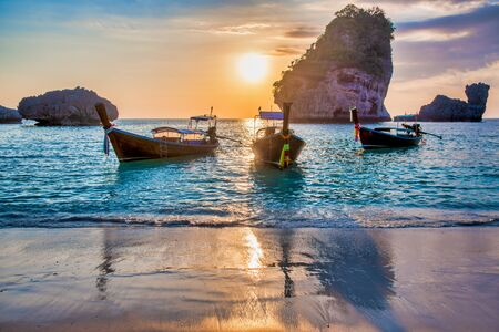 Koh Phi Phi Don with anchored long tail boats at sunset, Thailand. Vacation, travel and holiday concept. Фото со стока