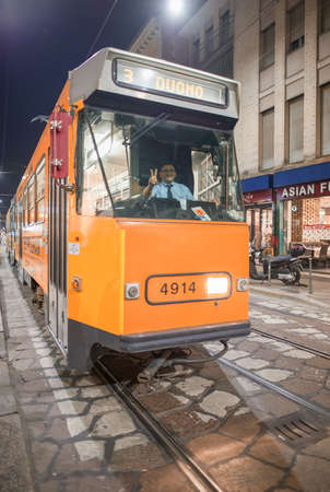 MILAN, ITALY - SEPTEMBER 2015: City tram speeds up along city streets at night. 에디토리얼