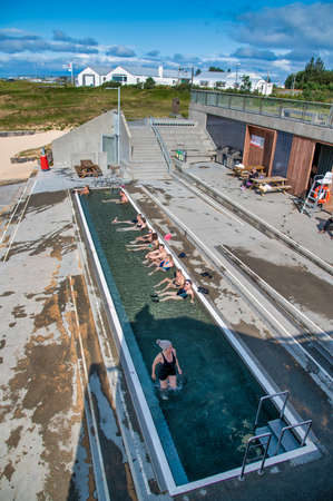 NAUTHOLSVIK, ICELAND - AUGUST 11, 2019:  Tourists enjoy beautiful geothermal baths along the sandy beach.