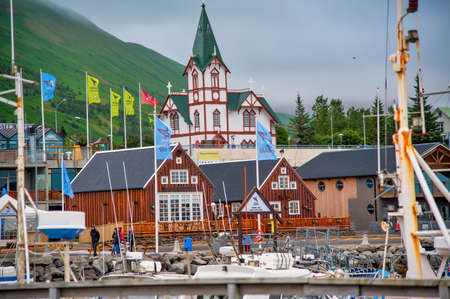 HUSAVIK, ICELAND - AUGUST 5, 2019: Husavik colorful homes and city port in Iceland. View on a cloudy summer afternoon.