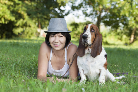 basset: The woman with a dog in the park, Selective focus and small depth of field, lens flare Stock Photo