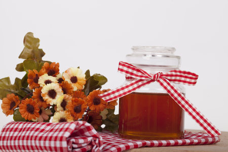 Honey in  jar with honey dipper on a light background Stock Photo