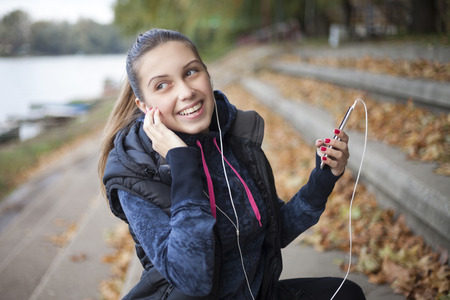 The young woman listens to music by the river