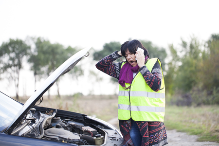 Woman call for help because of a malfunction the car on the road, Selective focus and small depth of field Stock Photo