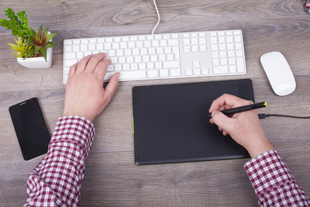 uses a computer: The graphic designer uses a digital tablet and computer Stock Photo