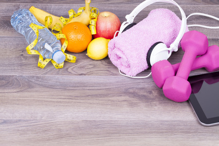 Fitness concept with towel,tablet, headphones, weights, bottle of water and fruit on a wooden background