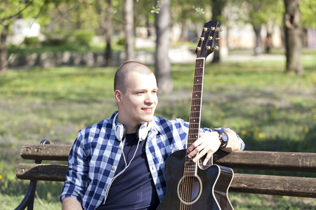 tiefe: Handsome young man enjoying the park with a guitar.Selective focus and small depth of field.