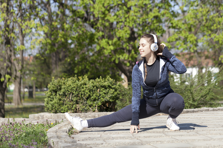 Beautiful young woman doing exercises and enjoys listening to music in the park. Selective focus and small depth of field. Stock Photo