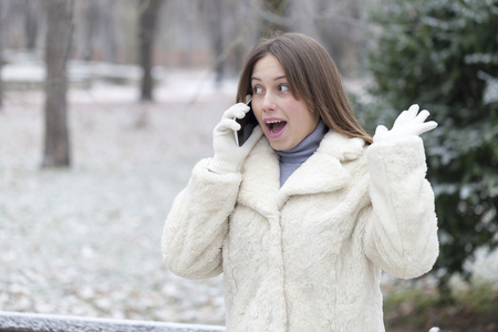 hear business call: Young woman phoning in the park, positively surprised and shows her happiness and satisfaction