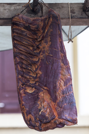 Home made smoked baconin in  one piece which is hanging  . Selective focus and small depth of field Imagens