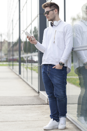 Handsome young man standing outside then and chat messages on a mobile phone. Selective focus and small depth of field. Stock Photo