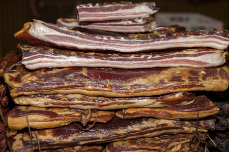 Homemade dried and smoked bacon exposed to the market, selective focus and small depth of field