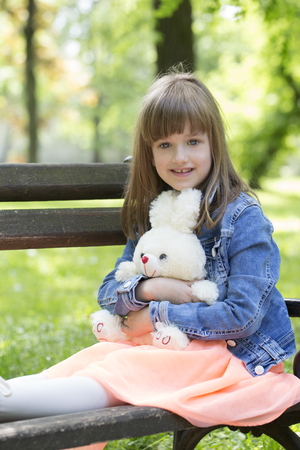 Little girl sits on a bench in the park and holding in the hands of her favorite stuffed toy