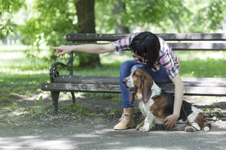 Woman sits on a bench in the park with his beautiful dog and shows him which way to look. Enjoy the beautiful day Stock Photo