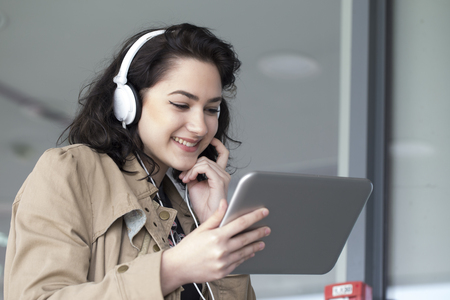 mladistvý: Young beautiful girl, student, listening to music and holds in her hand tablet.