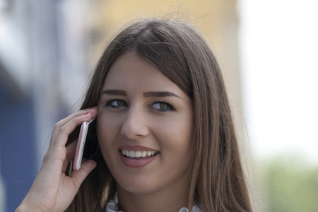 woman on phone: Young beautiful smiling woman talking on a mobile phone on the street in the city