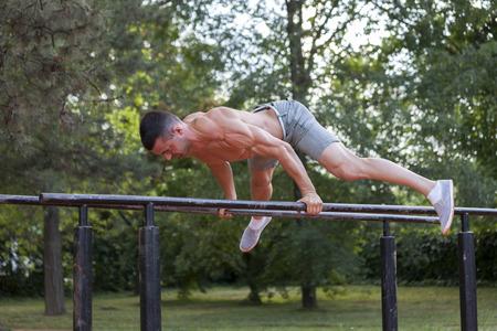 Jonge gespierde jonge man doet oefeningen op de parallelle staven in het park Stockfoto