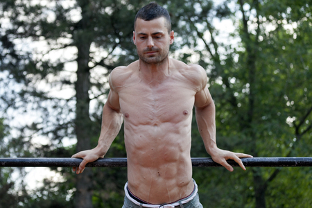 flexing: Exercise and fitness concept.Handsome young muscular man doing exercises on the horizontal bar