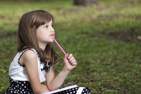 Cute little girl sits in nature, holding a notebook and a pen, and looking pensive Stock Photo