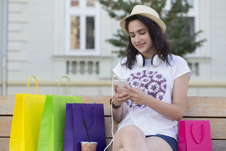 Young beautiful smiling girl, a teenager, with a hat resting on the bench after shopping. Next to her are full bags, things she bought. She holds a mobile phone in her hand and texting message.