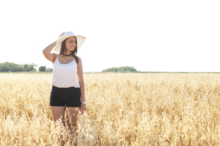 Portrait of a beautiful young woman with hat on the wheat field against blue sky