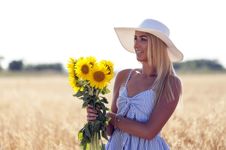 Close up portrait of a beautiful young woman with hat and blurred wheat field and sky on background.She holds a sunflower bouquet in her hand. They inspire the happiness and joy Stock Photo