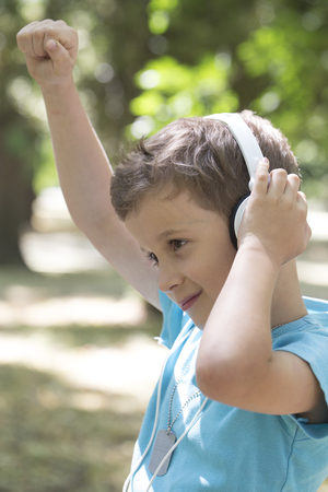 little cute boy of pre-school age listens to music and shows satisfaction. He raised his hand high and enjoy his favorite band