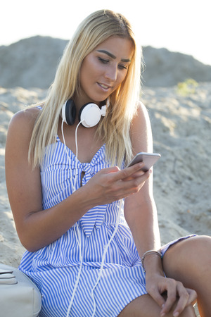 Young pretty girl in a dress sits on a sandy beach and using a mobile phone. Texting mesages Stock Photo