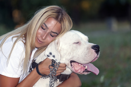 Young beautiful woman enjoying the embrace with her dog- Dogo Argentino.