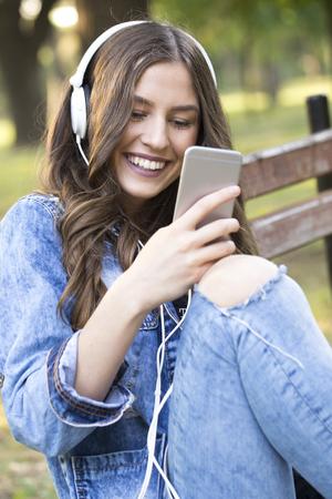 若い笑顔と美しい女性公園のベンチに座って音楽を聴く携帯電話を保持しています。音楽を聴きながら、彼女は彼女の友人に対応します。 レンズ フ