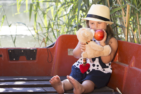 Little cute little girl with a hat is sitting in a boat on the lake and holding her favorite stuffed toy and apples in her hand. She plays and enjoys a beautiful sunny summer day. Childhood, growing up, healthy food