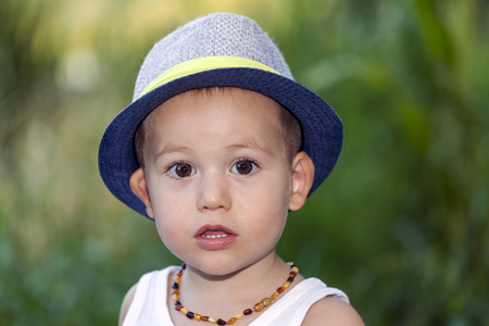 Portrait of a sweet little boy with a hat while standing outside on a beautiful sunny summer day. He plays out and looks into the camera. Copy space