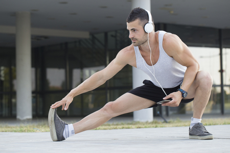 Male runner doing stretching exercise, preparing for morning workout outdoors. While doing a stretching exercise, he listens to music and holds a mobile phone in his hand. Banco de Imagens
