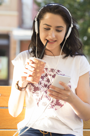 Beautiful young smiling girl- a teenager sitting on a park bench, listening to music and holding a mobile phone.She was holding a large plastic cup with juice. hipster style, outdoor portrait, happy face Stock Photo