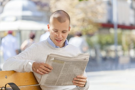 Young businessman sits at a table in the summer garden of a cafe and reads newspapers
