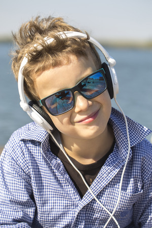 Portrait of a cute little boy with sunglasses, while listening to music. He enjoys a beautiful sunny day. He is very modern and attractive boy Stock Photo