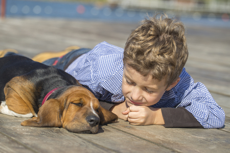Little cute boy lying by the river with his puppy. They enjoy together on a beautiful and sunny day. Growing up, love for animals - dogs, free time, travel, vacation