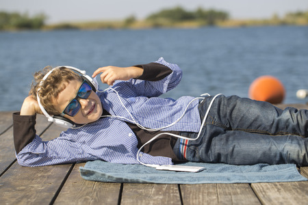 Portrait of a little sweet boy with sunglasses and headphones. He lies by the river, listens to music and enjoys a beautiful sunny day. He is a very modern and attractive boy